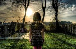 Image shows a little girl in a garden.