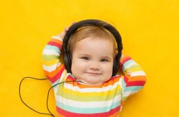 Image shows baby listening to headphones.