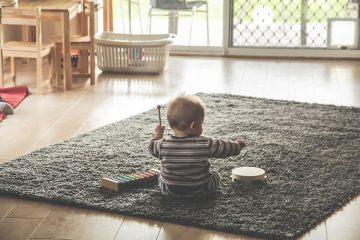Image shows a baby playing wiht a drum.