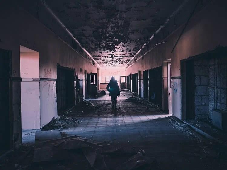 Image shows a person walking alone through a corridor.