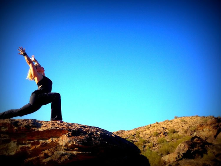 Image shows a woman in a yoga pose on a hill top.