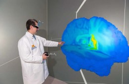 Image shows the researcher with a 3D image of a brain.