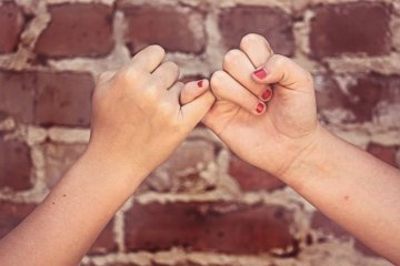Image shows a pinky swear.