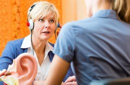 Image shows a woman taking a hearing test.