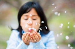 Image shows a woman blowing petals.