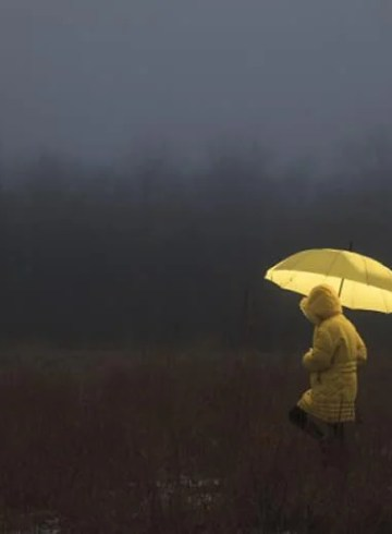 Image shows a woman walking in the rain.