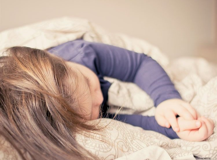 Image shows a little girl sleeping.