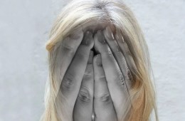 Image shows a female holding her head.