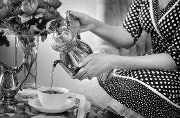 Image shows a woman pouring tea.
