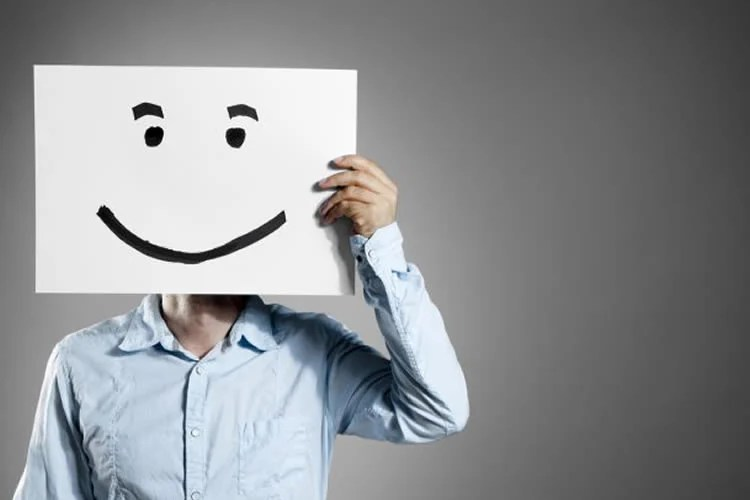 Image shows a man holding up a card with a smiley face on it.