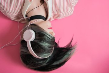 Image shows a girl listening to music.