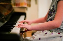 Image shows a little girl playing the piano.