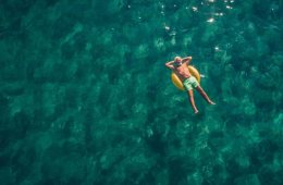 Image shows a man relaxing on a floatie in the ocean.