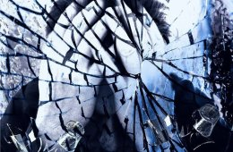 Image shows a person behind smashed glass.
