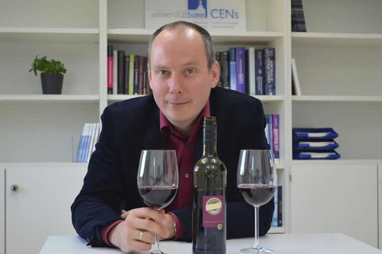 Image shows the professor and two glasses of red wine.