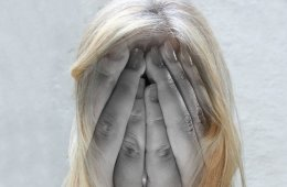 Image shows a woman holding her head in pain.