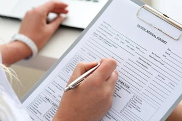 This image shows a person filling out a medical document.