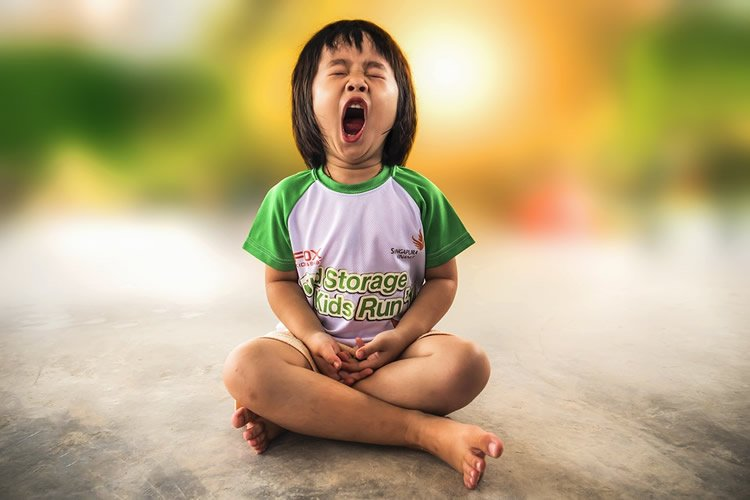 Image shows a child yawning.