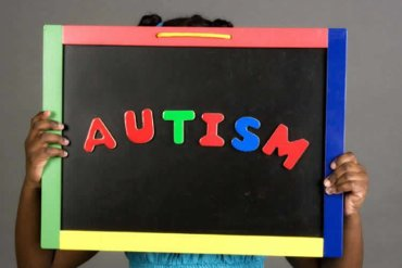 Image shows a girl holding up an autism sign.