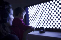 Image shows a child by a light up wall