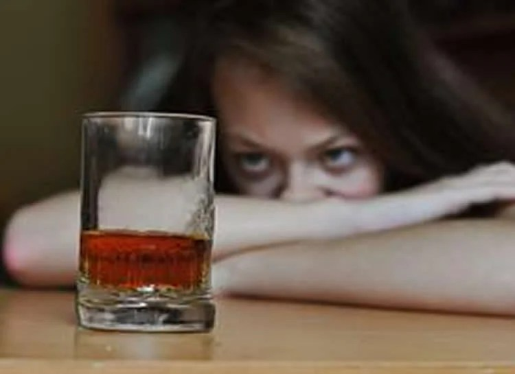 Image shows a woman looking at a drink of whiskey.