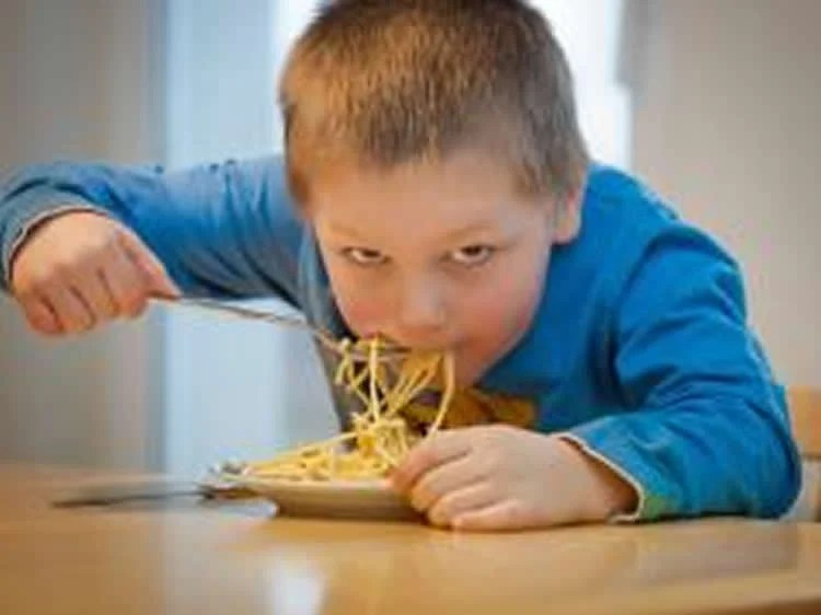 Image shows a boy eating.