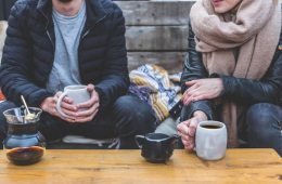 Image shows a couple drinking coffee.