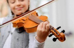 Image shows a woman playig the violin.