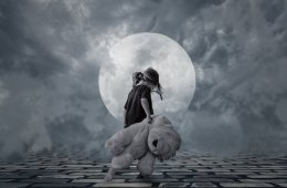 Image shows a lonely child carrying a teddy.