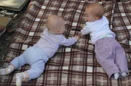 Image shows babies on a blanket.