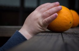 a child grabbing an orange