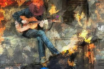Image shows a person playing guitar.