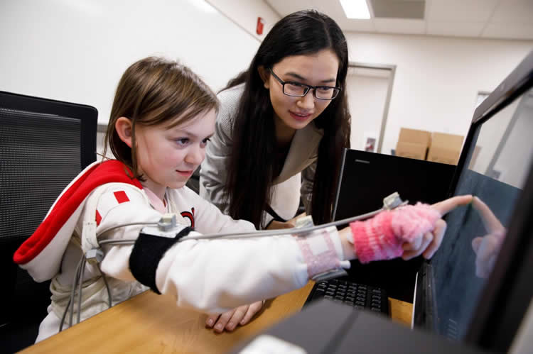 Image shows the researcher and a little girl.