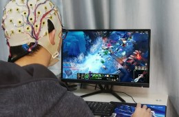 Image shows a person wearing an EEG cap playing a computer game.