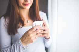 Image shows a woman on using a smartphone.