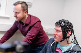the researcher and a participant in an EEG helm