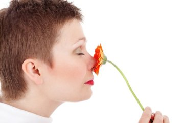 a woman smelling a plastic flower
