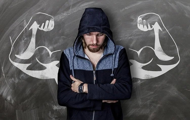a man with muscular arms drawn behind him on a blackboard