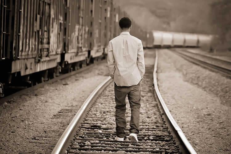 boy walking on train tracks