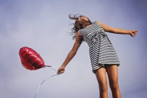 A person in a dress is shown holding a balloon.