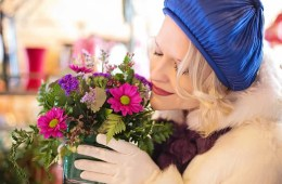This shows a woman smelling flowers