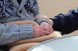 This shows someone holding an old person's hands