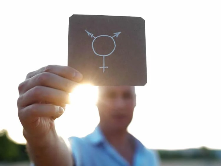 This shows a person holding up a gender sign on a piece of paper