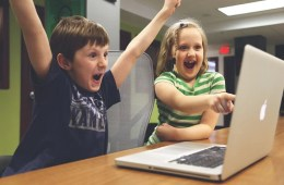 This shows a young girl and boy playing a video game