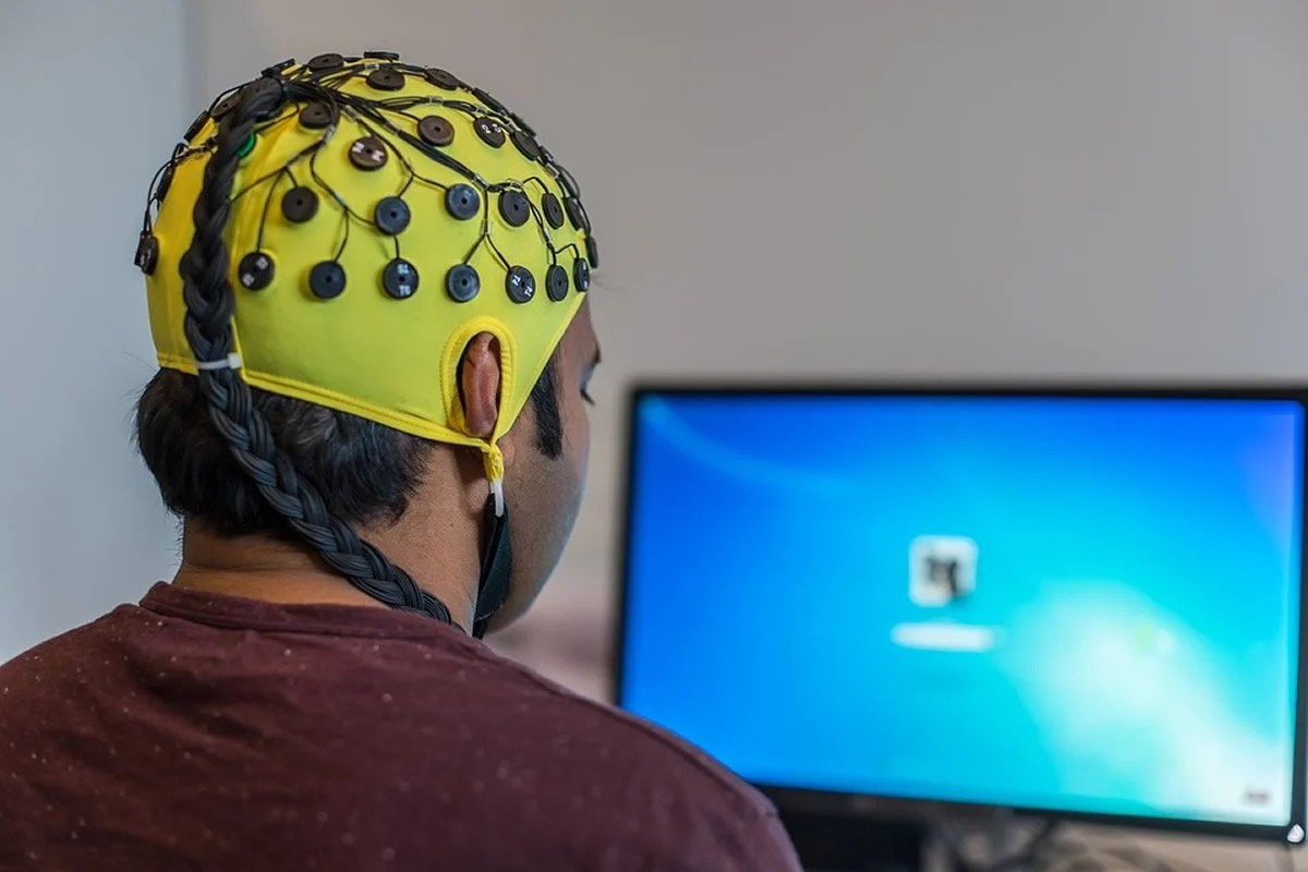 This shows a man in an EEG cap