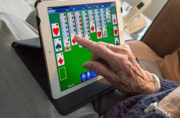 This shows an old man playing cards on a computer