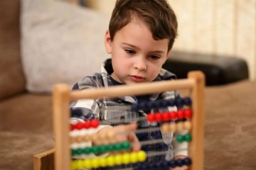 This shows a child with an abacus