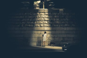 Image shows a child standing under a street lamp alone