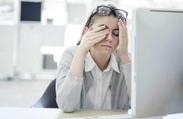 This shows a woman sitting at her desk, rubbing her eyes