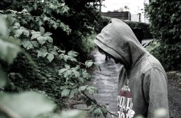 This shows a depressed looking man wearing a hoodie to cover his face